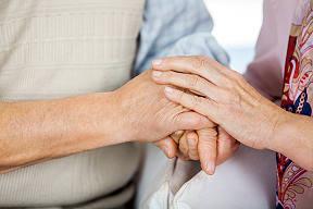 home care aide holding hand of elderly man